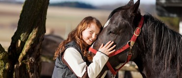 Portrait of a smiling young girl with a dark bay horse with red reins